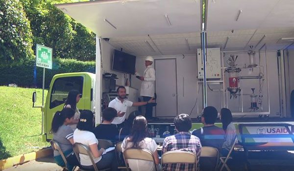 """Students listening to the explanation of biodiesel generation in the """"Steam Truck"""""""